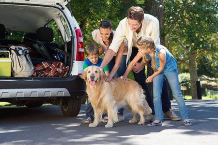 mujer con perro: Familia feliz que consigue listo para viaje por carretera en un día soleado Foto de archivo