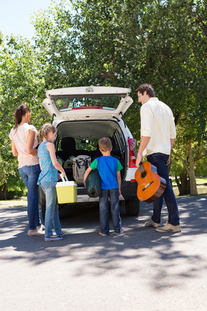 adult child: Happy family getting ready for road trip on a sunny day
