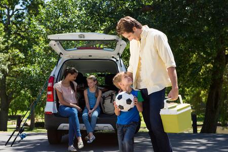 Familia feliz que consigue listo para viaje por carretera en un día soleado