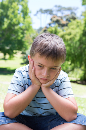 dreariness: Little boy feeling sad in the park on a sunny day Stock Photo