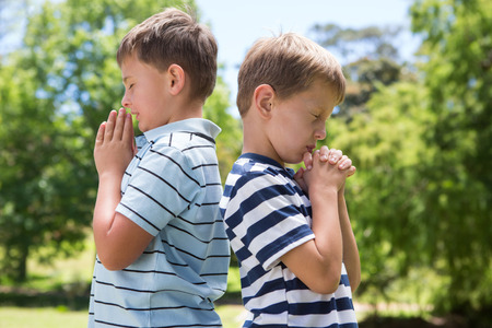 brethren: Little boys praying in the park on a sunny day Stock Photo