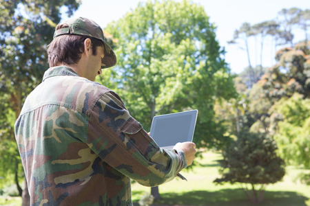 army uniform: Soldier looking at tablet pc in park on a sunny day Stock Photo
