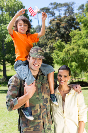 military uniform: American soldier reunited with family on a sunny day