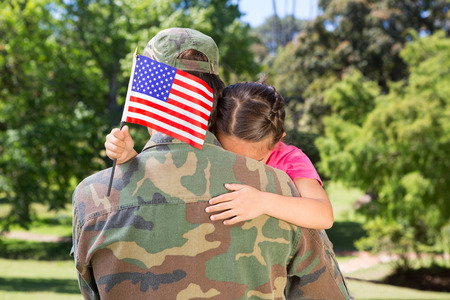military uniform: American soldier reunited with daughter on a sunny day