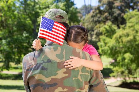 Amerikaanse soldaat herenigd met dochter op een zonnige dag Stockfoto