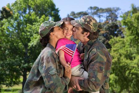 ?  ?       ?  ?      ?  ?     ?  ?    ?  ? �female: Padres Ej�rcito reunieron con su hija en un d�a soleado Foto de archivo