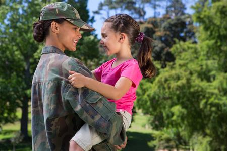 kinderen: Soldaat herenigd met haar dochter op een zonnige dag Stockfoto