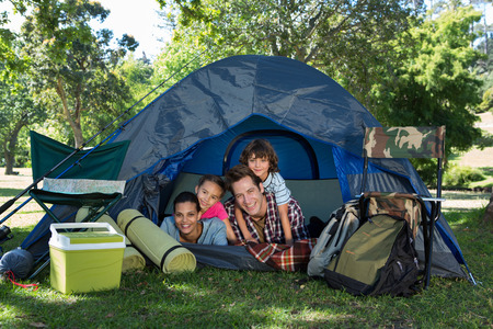 camping tent: Happy family on a camping trip in their tent on a sunny day Stock Photo
