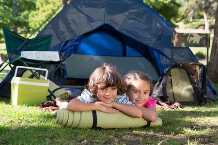 Glückliche Geschwister auf einem Camping-Ausflug an einem sonnigen Tag Lizenzfreie Bilder