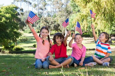 晴れた日にアメリカの国旗を振っている幸せの小さな友達 写真素材 - 36405683