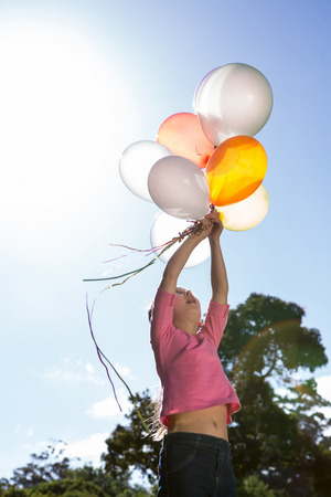 escapism: Happy little girl holding balloons on a sunny day
