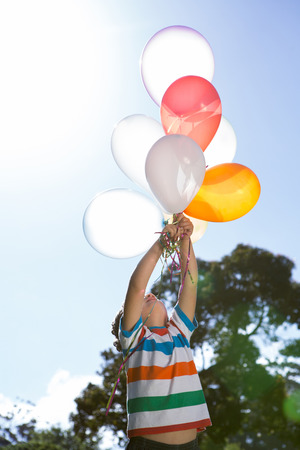 escapism: Happy little boy holding balloons on a sunny day