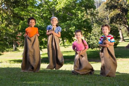 caucasian race: Children having a sack race in park on a sunny day