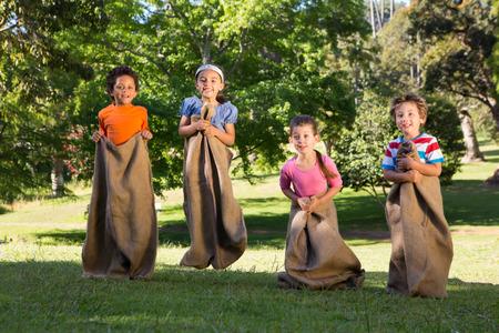 competencia: Los ni�os que tienen una carrera de sacos en el parque en un d�a soleado Foto de archivo