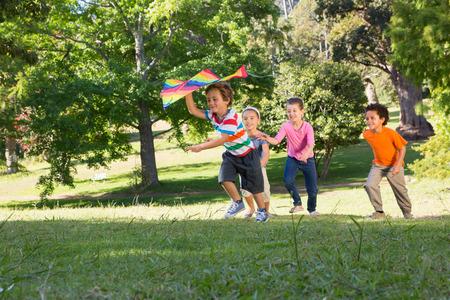 niños jugando en el parque: Niños jugando con la cometa en el parque en un día soleado