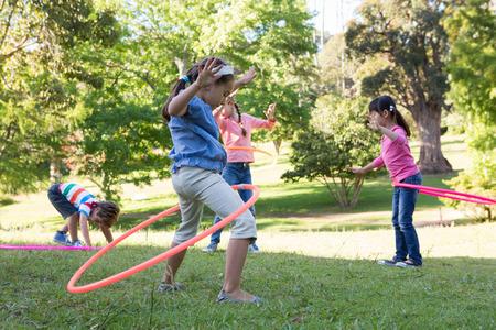 niños jugando en el parque: Pequeños amigos jugando con aros de hula en el parque en un día soleado