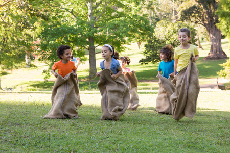 recreational pursuits: Children having a sack race in park on a sunny day