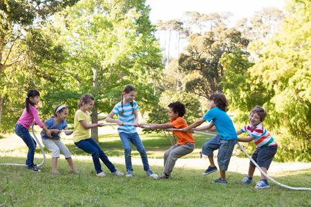 Children having a tug of war in park on a sunny day Foto de archivo