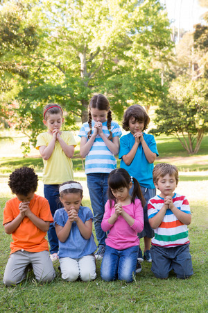 Children saying their prayers in park on a sunny day