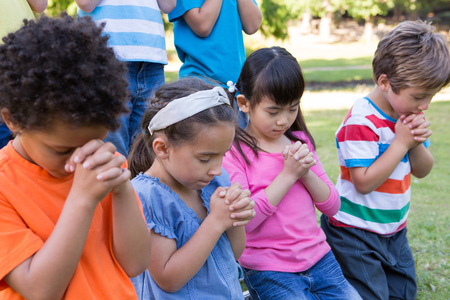 head in hands: Children saying their prayers in park on a sunny day