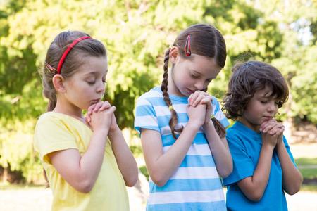 manos orando: Los niños diciendo sus oraciones en el parque en un día soleado