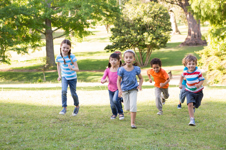 enfant qui joue: Enfants de course dans le parc sur une journée ensoleillée