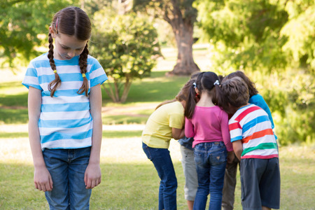 exclusion: Little girl feeling left out in park on a sunny day Stock Photo
