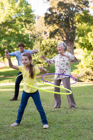 extended family: Extended family playing with hula hoops on a sunny day