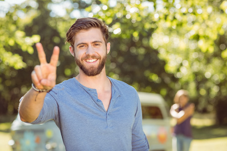 peace sign: Handsome hipster smiling at camera on a summers day Stock Photo