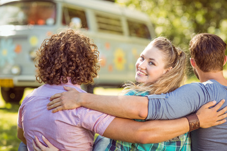 summers: Hipster smiling at camera with friends on a summers day Stock Photo