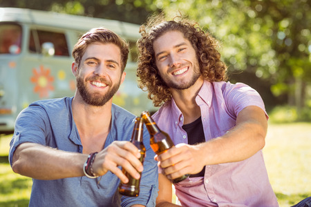 summers: Hipster friends toasting with beers on a summers day
