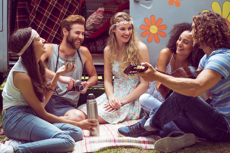 spring festival: Hipster friends by camper van at festival on a summers day