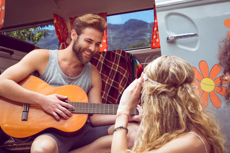 serenading: Hipster playing guitar for girls on a summers day
