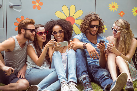 escapism: Hipster friends using their phones on a summers day