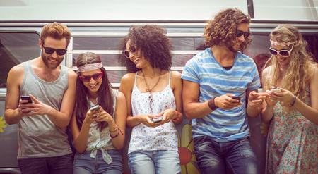 sol radiante: Hipster amigos utilizando sus teléfonos en un día de verano Foto de archivo