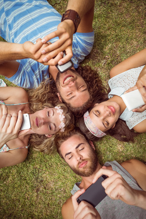 mobile phone: Hipsters lying on grass smiling on a summers day