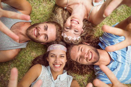 friendship tree: Hipsters lying on grass smiling on a summers day