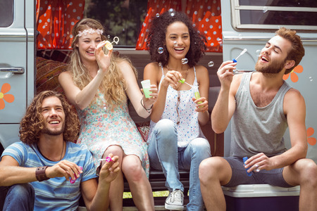 blowing bubbles: Hipsters blowing bubbles in camper van on a summers day