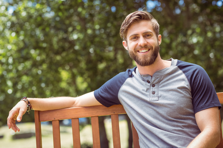 young man smiling: Young man relaxing on park bench on a summers day