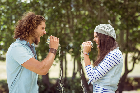 tin cans: Young couple shouting through tin cans on a summers day Stock Photo