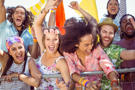 Excited young people singing along at a music festival Stock Photo