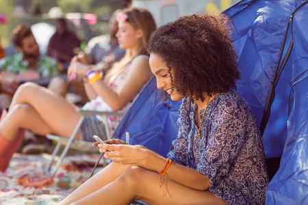 summer festival: Carefree hipster sending text message at a music festival Stock Photo