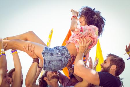 menschenmenge: Glückliche Hippie-Frau, Crowd Surfing an einem Musikfestival