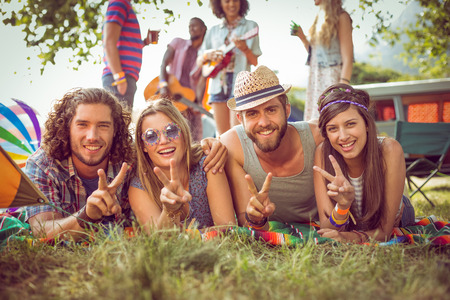 escapism: Happy hipster couples on campsite at a music festival