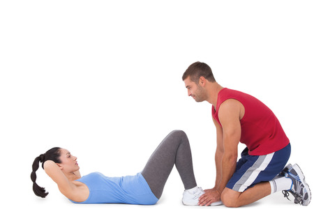 Trainer with woman doing sit ups on white background