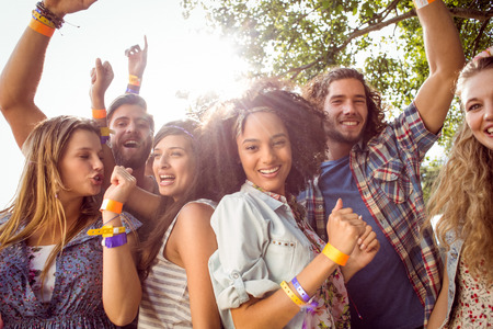 male friends: Happy hipsters dancing to the music at a music festival Stock Photo