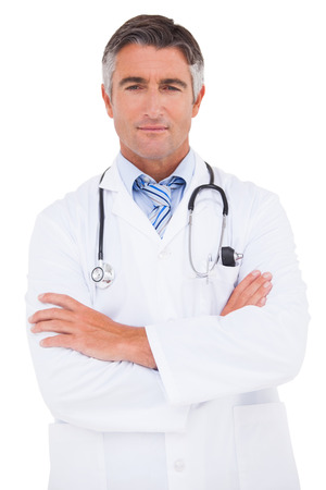 crossed arms: Serious doctor looking at camera on white background