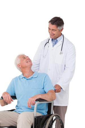 paraplegic: Doctor que empuja al paciente mayor en silla de ruedas en el fondo blanco