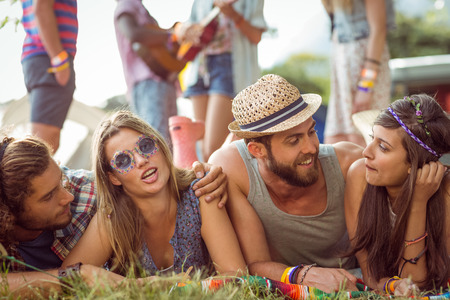 escapism: Happy hipsters chatting on the campsite at a music festival