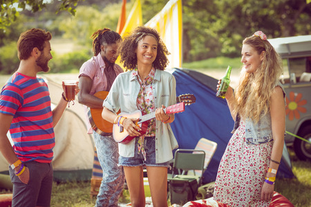 social drinking: Happy hipsters having fun on campsite at a music festival